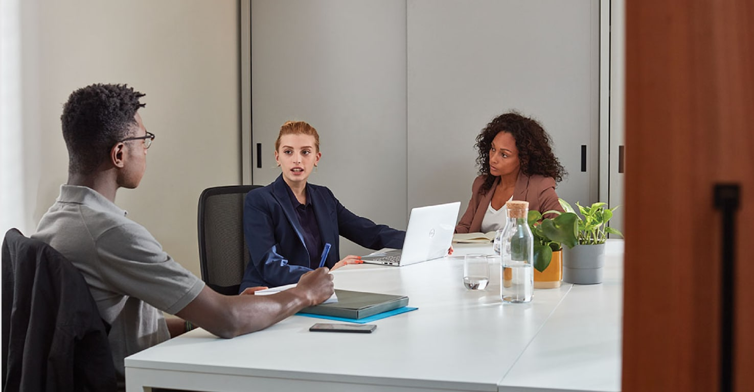 Three people having a meeting around a table.