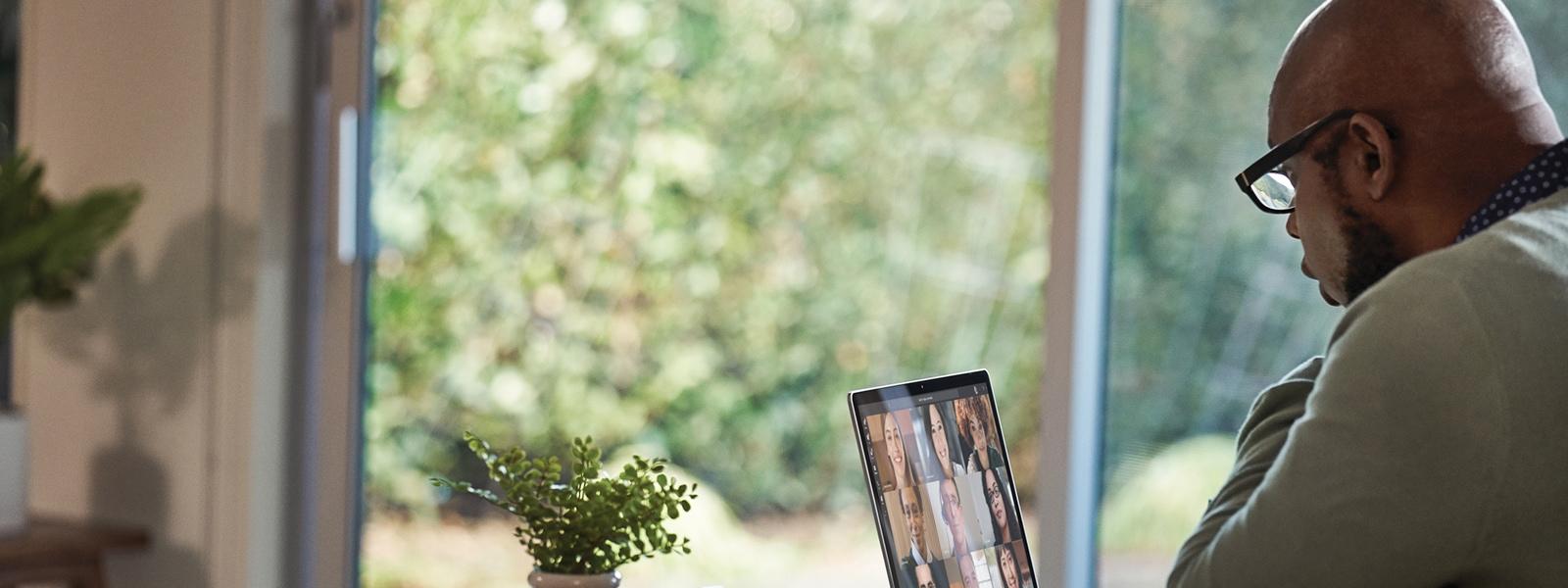 Una persona usa un portatile per una videochiamata davanti a una grande finestra.