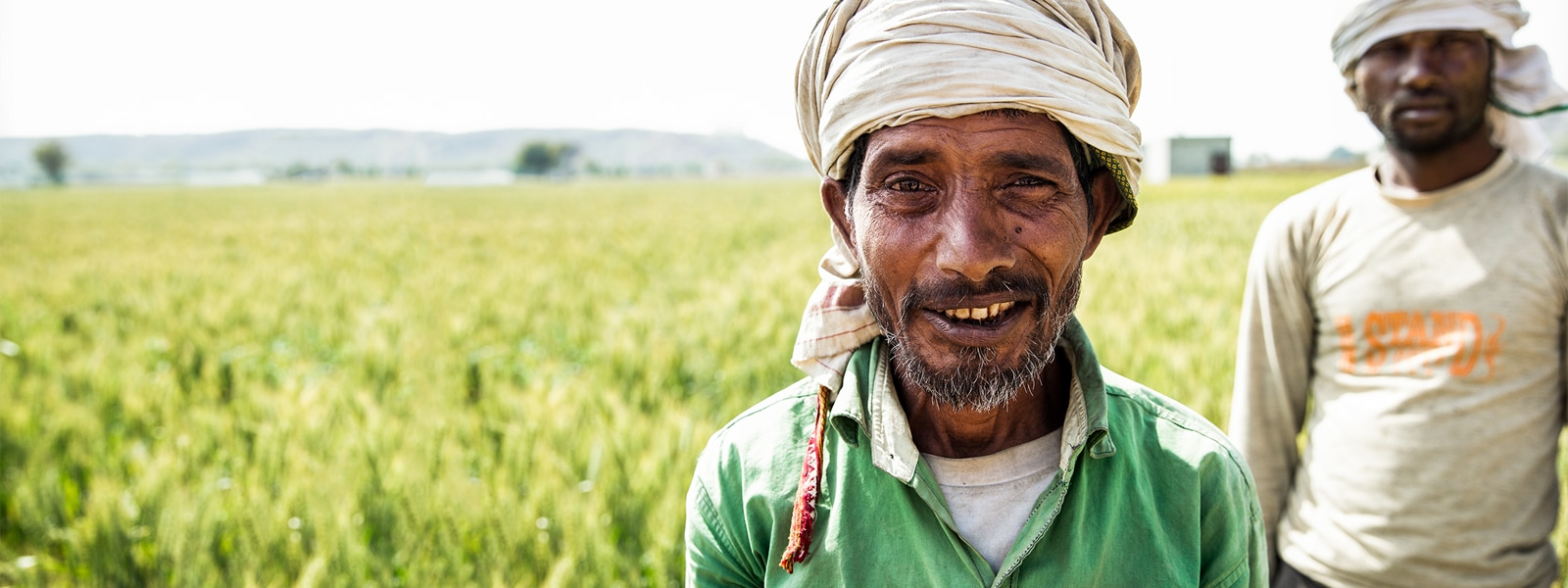 Two Indian farmers smiling in a field
