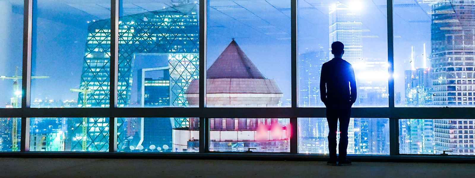 Man stands in a windowed office overlooking a city at night