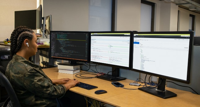 A person working at a desk with three monitors.