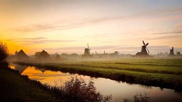 A sunset over a field with a river and windmills.