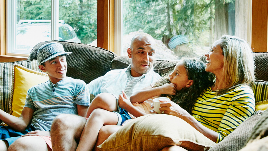 Photo credit: Thomas Barwick/DigitalVision/Getty Images. Family of four sits together on a couch at home