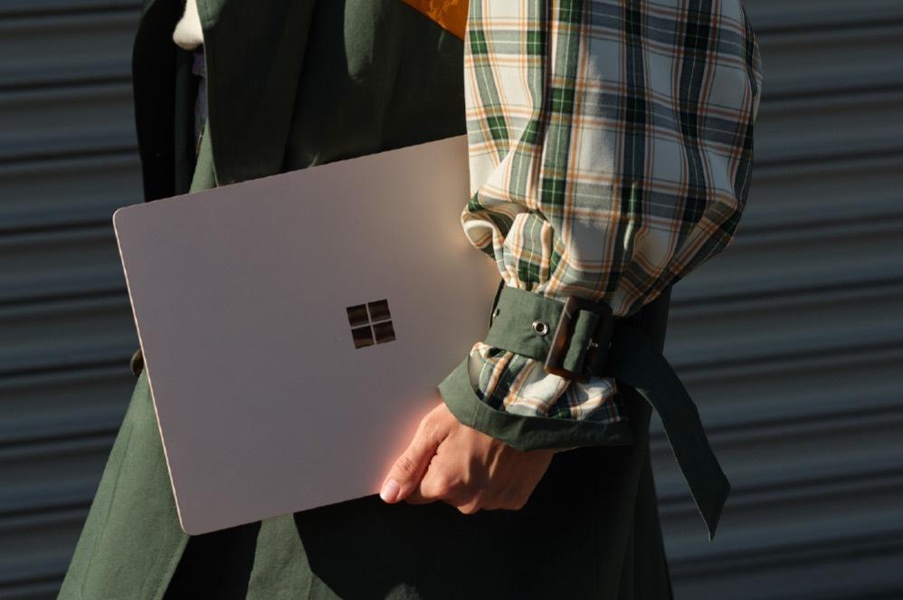 一个人拿着屏幕闭合的 Surface Laptop 3