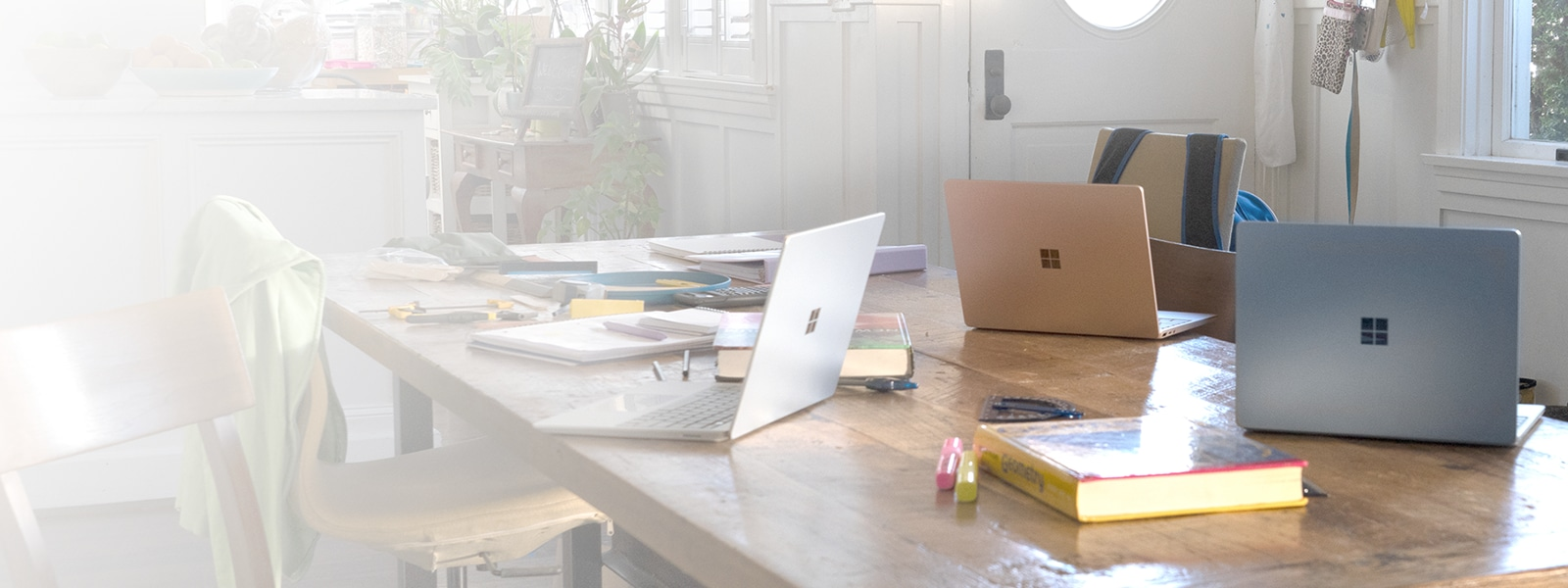 Three Surface Laptop Go sitting on a kitchen table cluttered with textbooks and school supplies