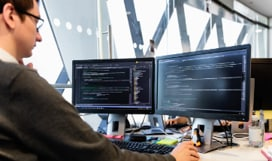 A person looking at two monitors at their desk.