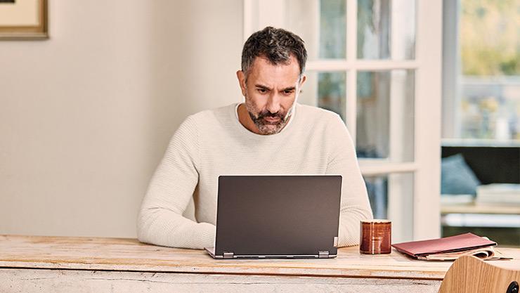 Un homme utilise un ordinateur portable chez lui, assis à une longue table en bois.