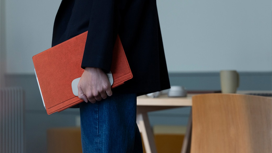 شخص يحمل جهاز Surface Pro 7 مع لوحة مفاتيح Surface Type Cover مغلقة وماوس Surface