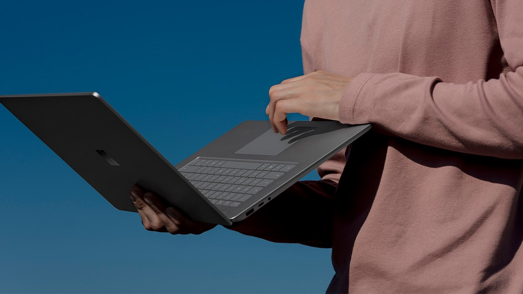 Person holding Surface Laptop 3 while using the trackpad