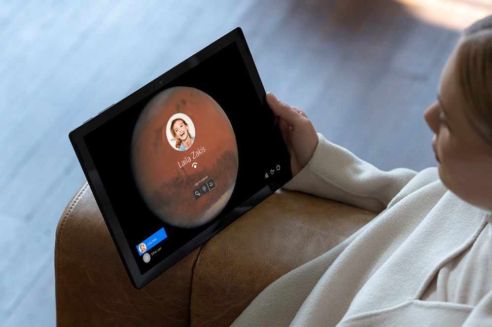 Una persona sostiene Surface Pro 7 y mira a la pantalla de inicio de sesión