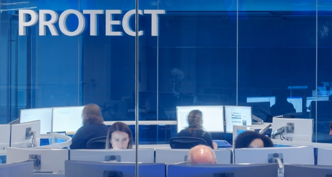 An office with multiple people working at their desk and the word Protect is in the top left corner.