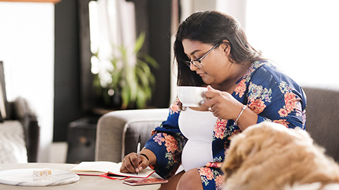 Woman on couch writes in a journal while drinking coffee