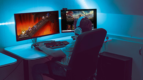Gamer sitting at a desk using a computer and two monitors