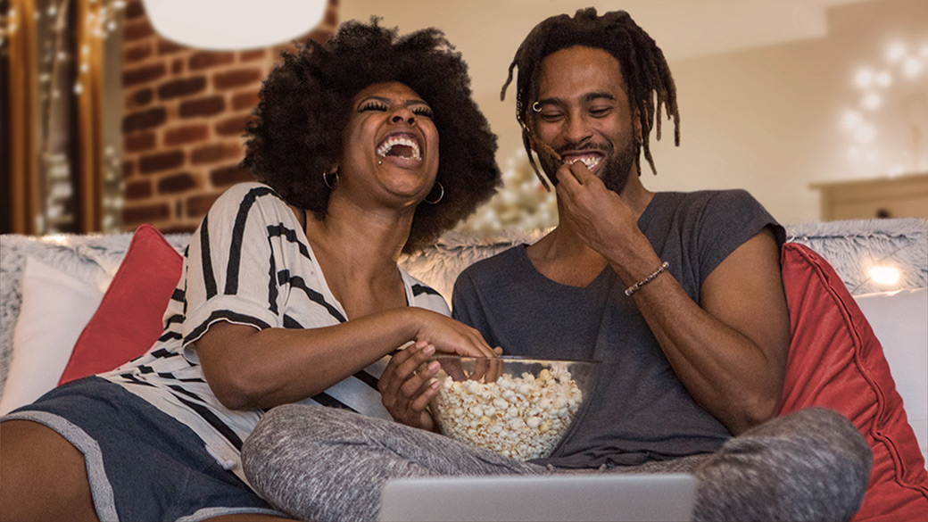 Laughing man and woman eat popcorn together on the couch at home while watching a video conference on laptop computer