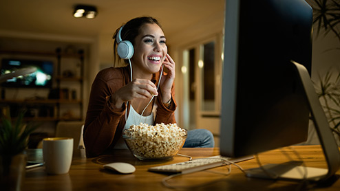 Woman wearing headphones and eating popcorn while watching a movie online