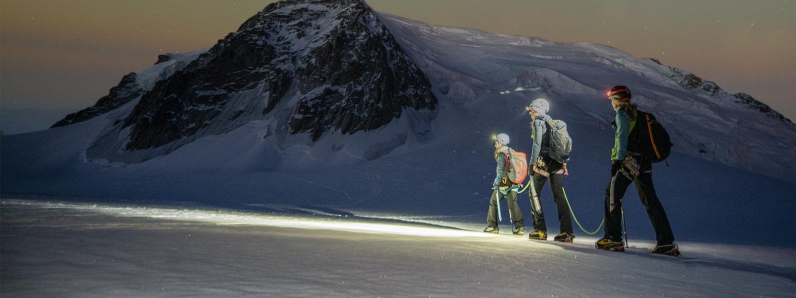 Drei Wanderer überqueren in den Bergen ein Schneefeld unter freiem Sternenhimmel.