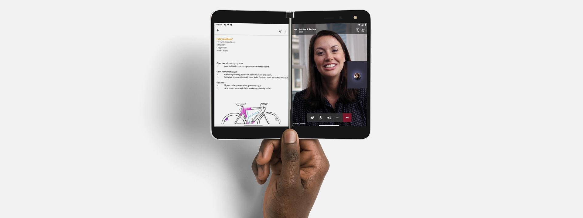 Eén hand houdt de twee schermen van een Surface Duo open