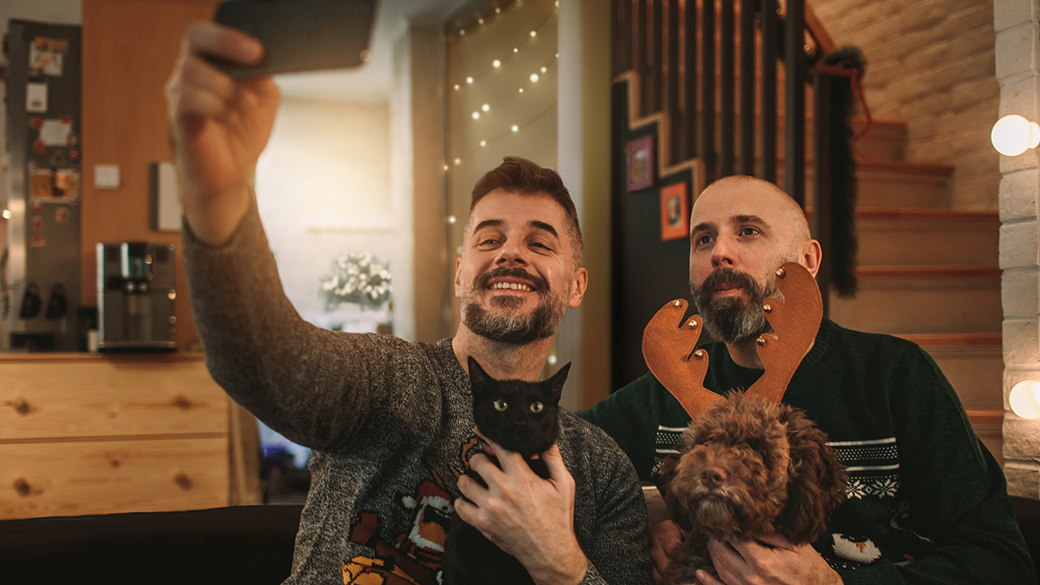 Two men photograph themselves at home while holding a cat and a dog
