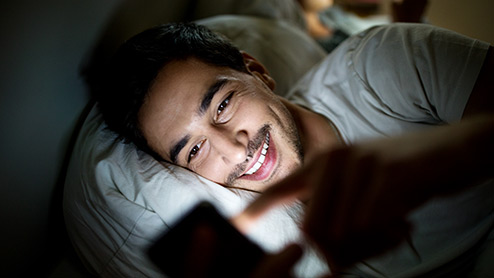 Smiling man uses mobile device while in bed at night