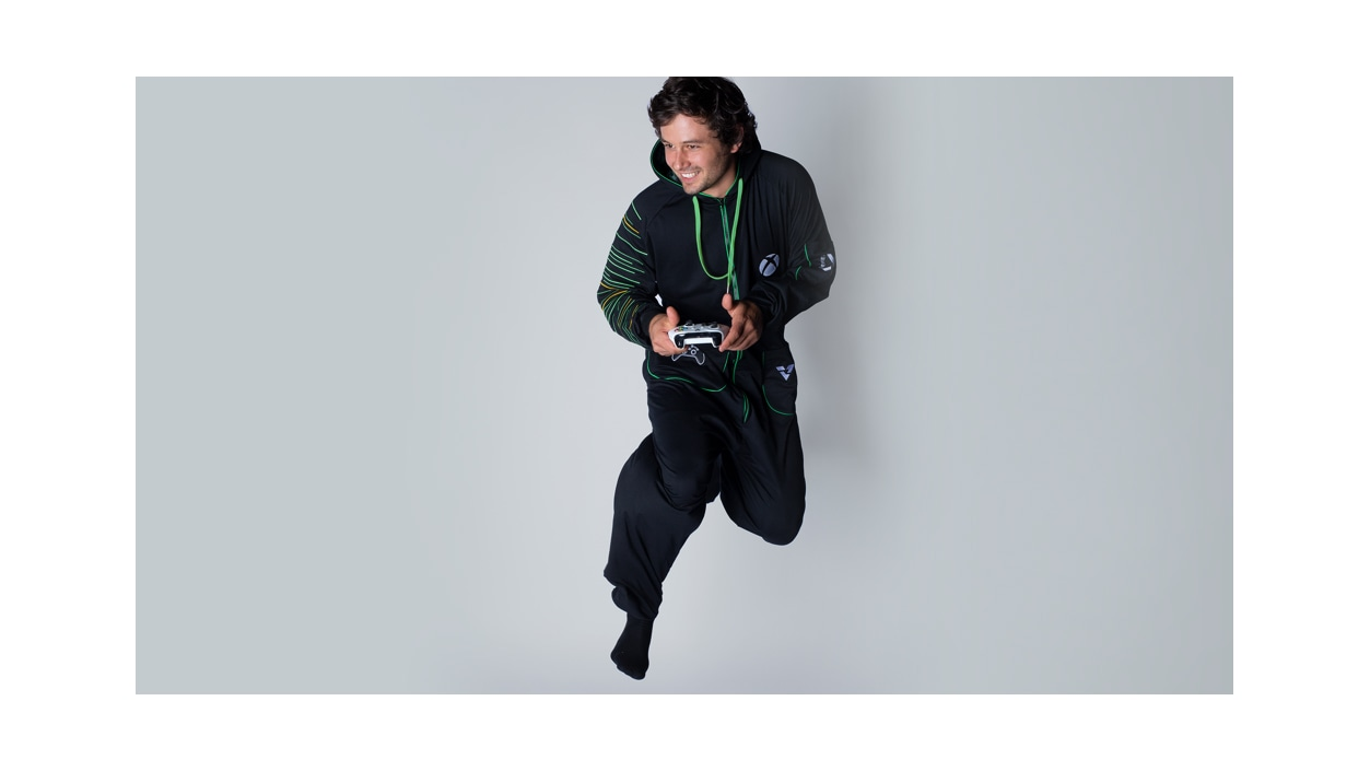 Male wearing Xbox Series X Hooded Union Suit and holding a Xbox Wireless Controller