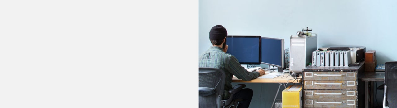Back view of man sitting at workstation with multiple monitors.