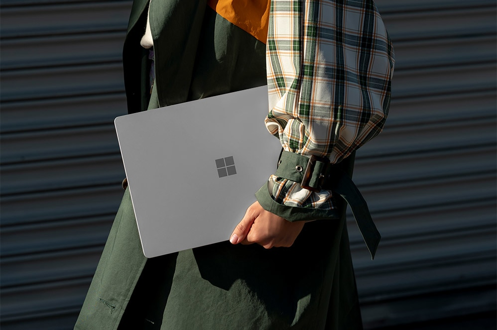 Person, der holder Surface Laptop 3 med skærmen lukket