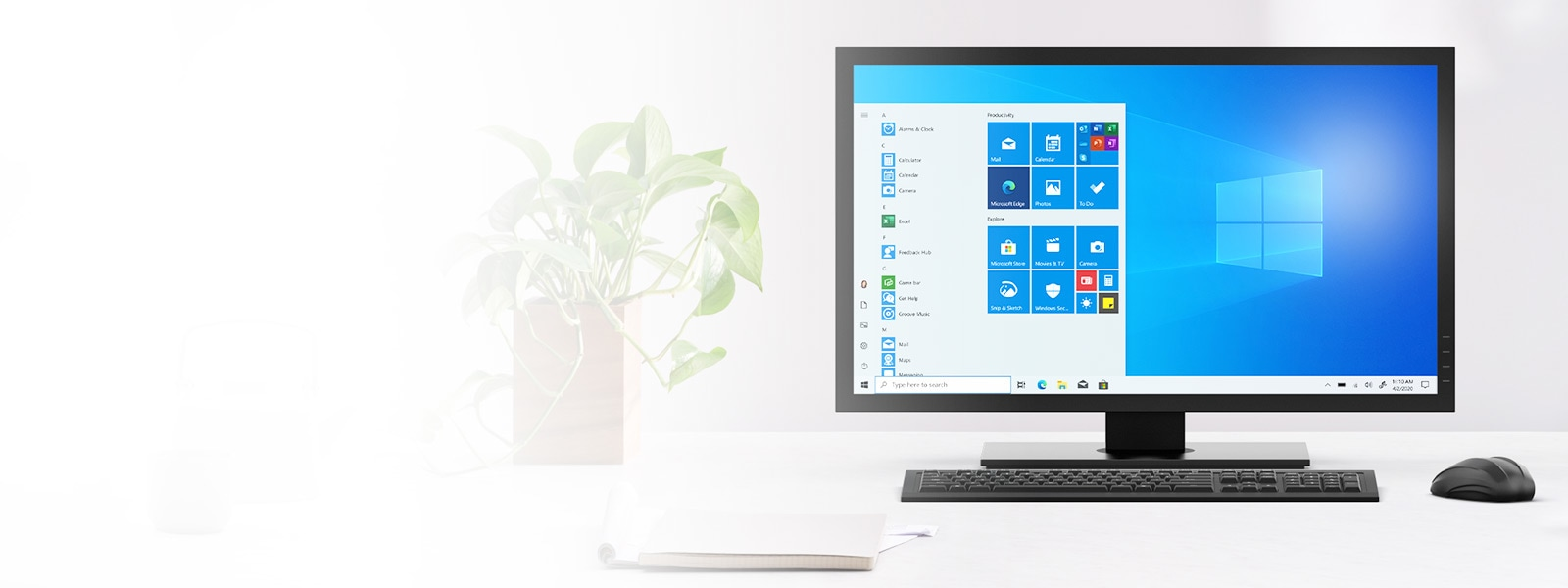 A Windows 10 all in one sits on a desk with a mouse and notepad nearby