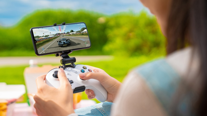 Person holding Xbox Wireless Controller with mobile device attached to it