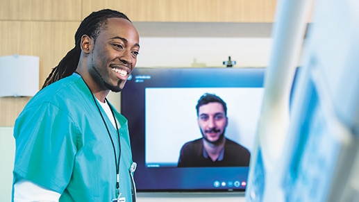 A healthcare professional speaking to a patient while a person is watching on video call on Teams.