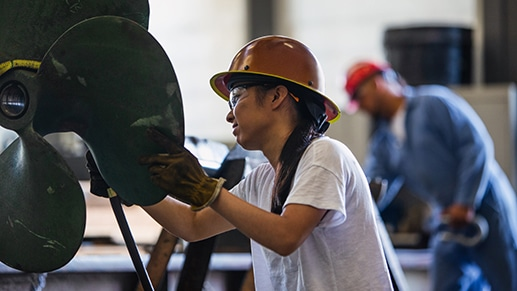 A Firstline Worker wearing personal protective equipment works on a large propeller. Another Firstline Worker appears out of focus in the background.