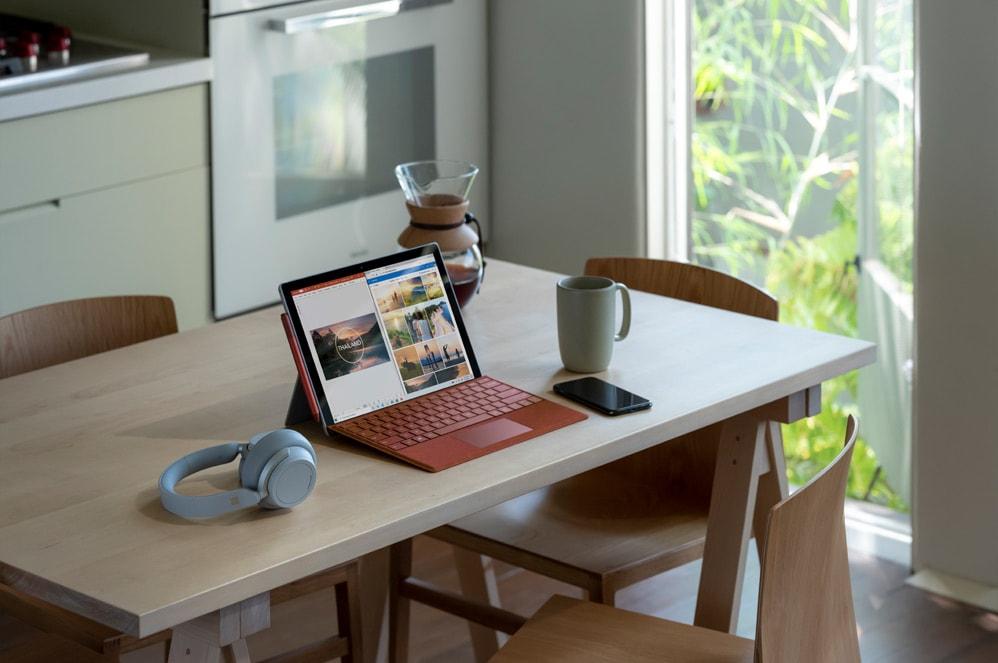 桌上的 Surface Pro 7 旁邊放著 Surface Headphones 2 和手機