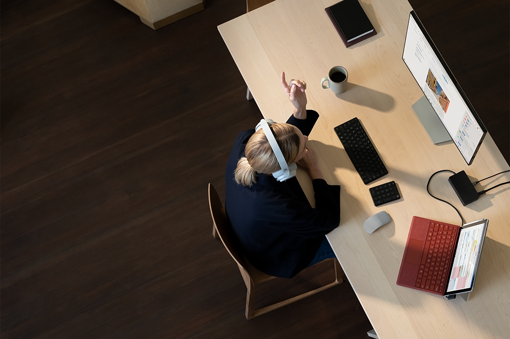 Overhead view of person sitting at desk working with Surface Pro 7+ for Business and keyboard, monitor, and adapter.
