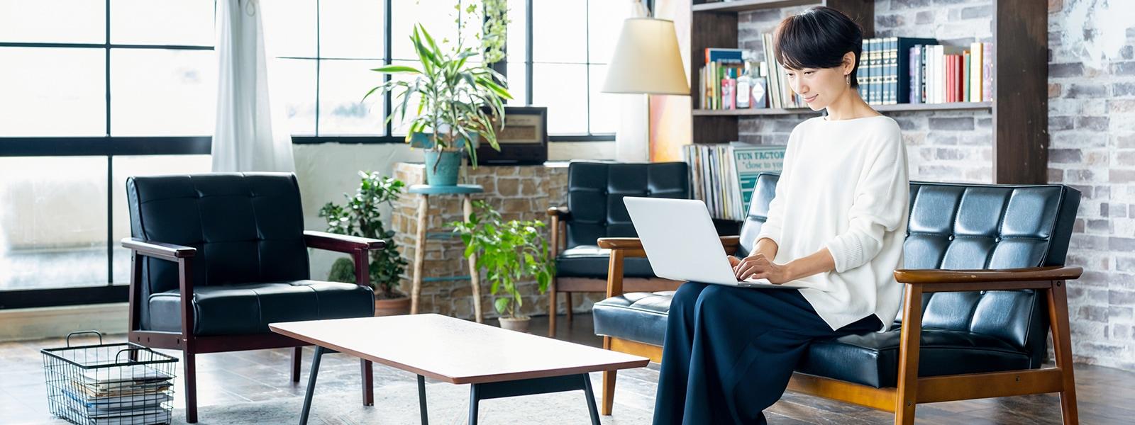 リビングのソファに座り膝の上のノート PC を操作する女性