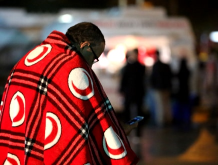 A person wearing a Turkish Red Crescent blanket over their shoulders.