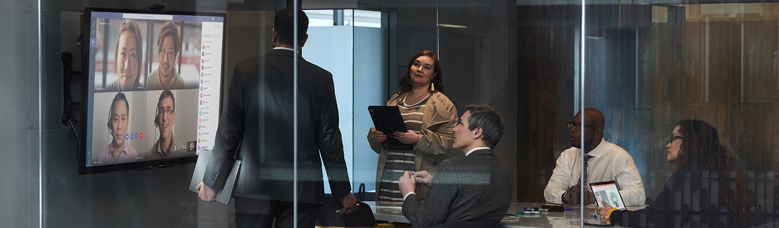 A group of people in a glass office on a Teams video call.