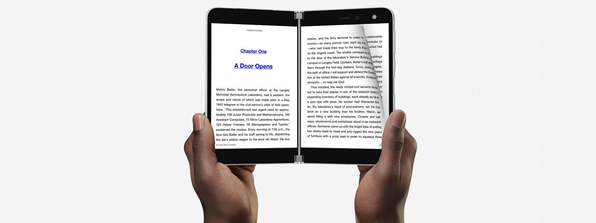 A pair of hands holding up Surface Duo with Kindle