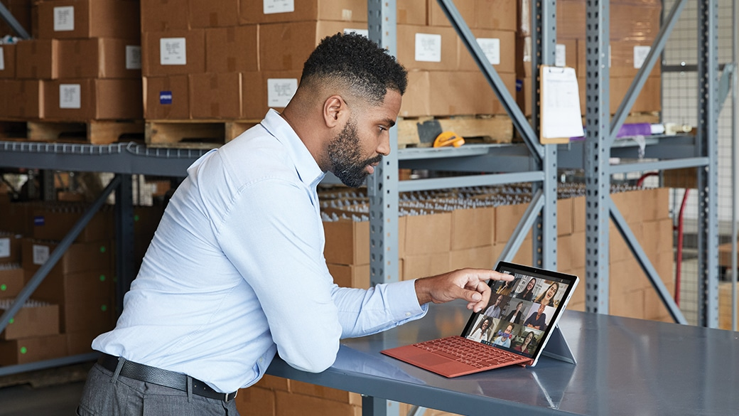 Person standing at a table using Surface Pro 7+ for Business.