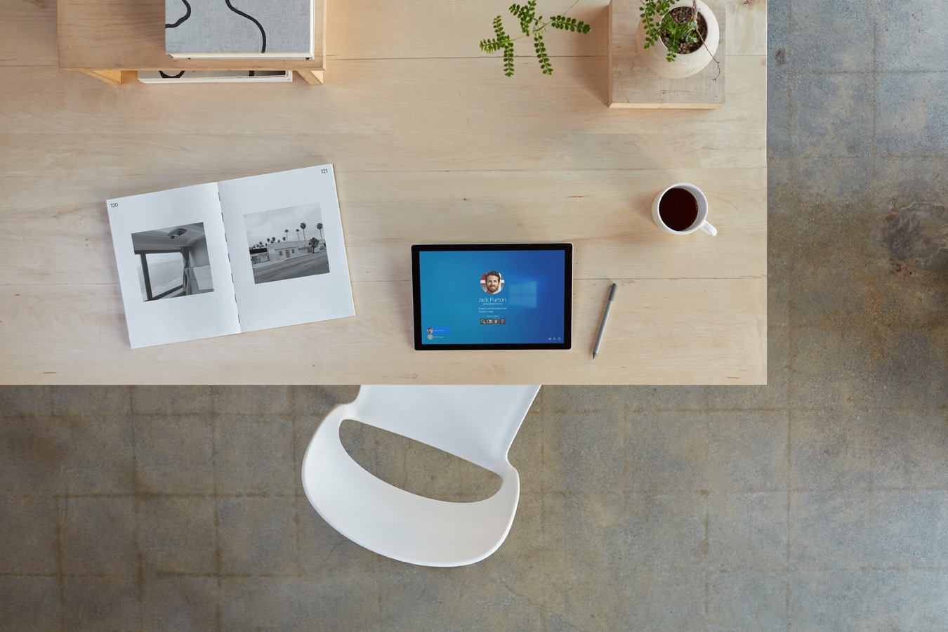 A top down view of a Surface Pro 7+ device on a home office desk surrounded by accessories