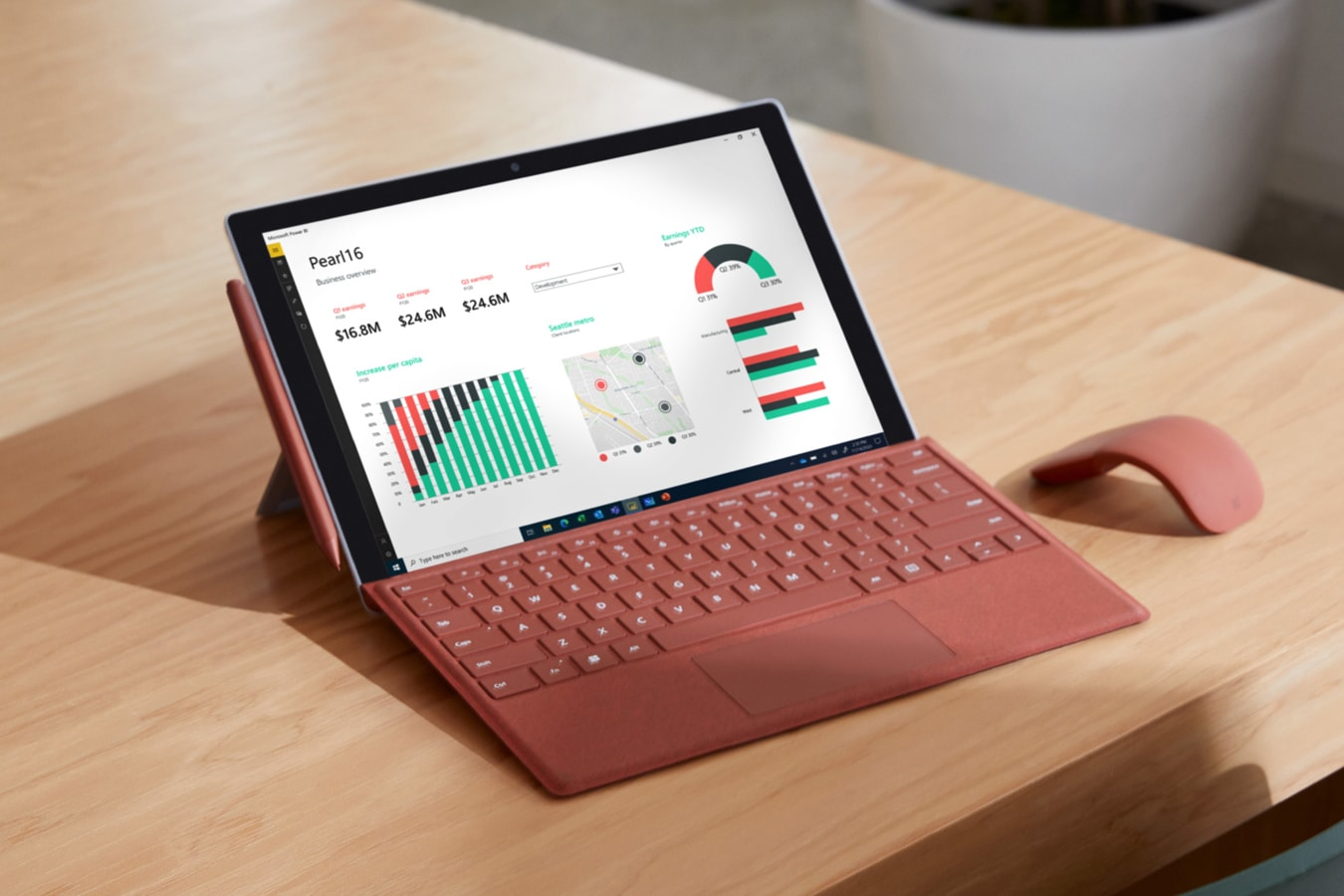 Surface Pro 7+ is pictured on a home office desk with Surface Pro X Signature Type Cover attached, Surface Pen and Surface Arc Mouse all in Poppy Red colour.