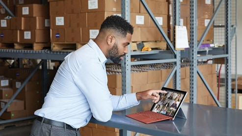 A person interacts with their Surface Pro 7+ while in a virtul meeting