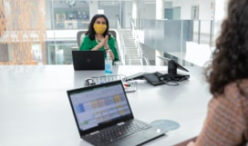 Two people wearing masks having an in person meeting in an office.