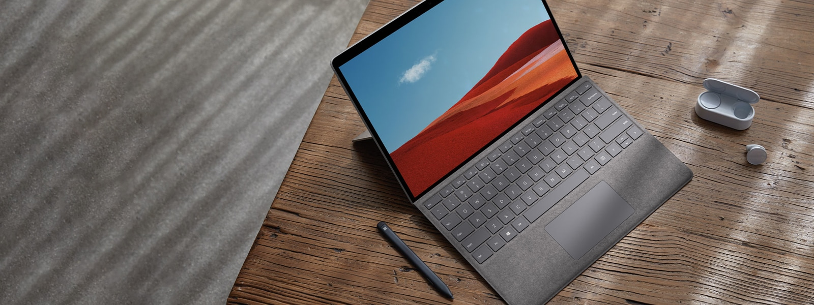 Surface Pro X inside alone on desk with Surface Earbuds and Surface Slim pen