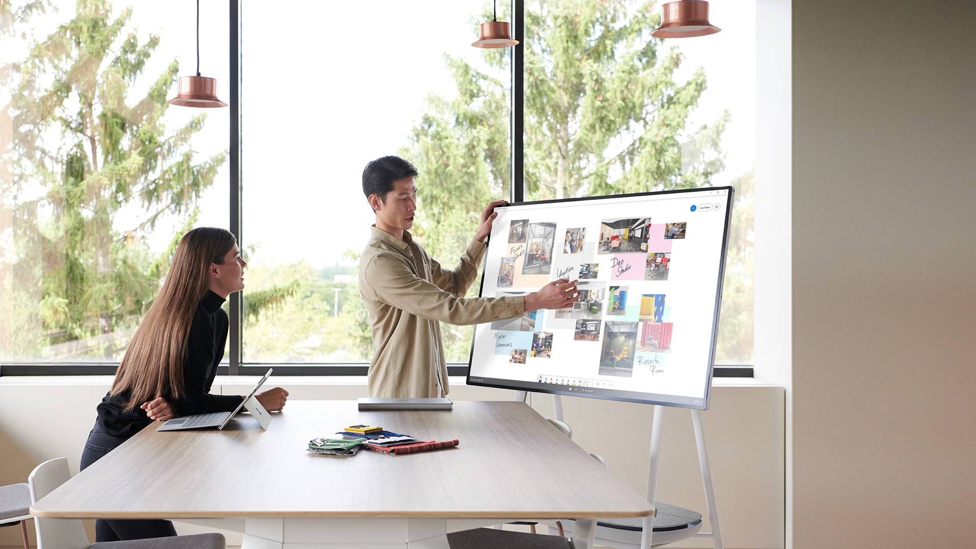 Colleagues gather around the Hub 2S 50-inch device