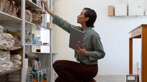 A woman holds her Surface device while reaching for something on a shelf from a kneeling position