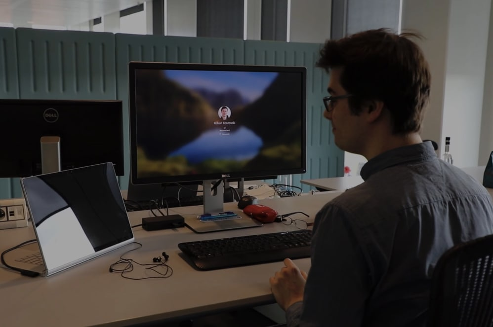 Man in front of two computer screens with code on it