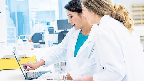 Zwei Frauen in weißen Krankenhauskitteln arbeiten gemeinsam an einem Laptop