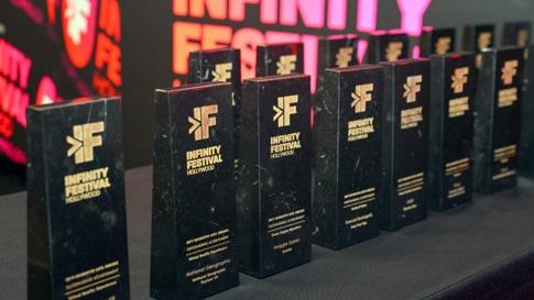Eine Gruppe von Infinity Festival Awards, die in zwei Reihen aufgestellt wurden.