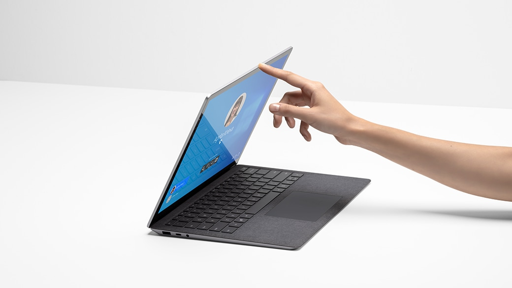 A person's hand with finger lifting the lid of Surface Laptop 4 for Business.