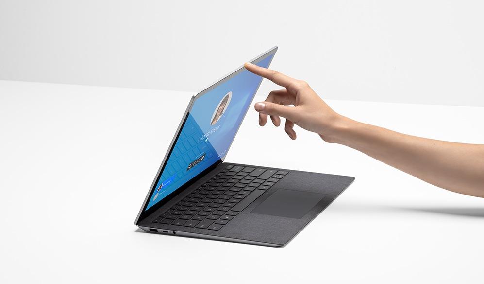 Main d'une personne avec un doigt soulevant l'écran du SurfaceLaptop4 pour les entreprises.