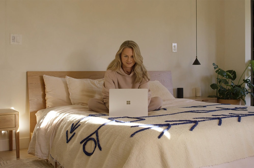 A person uses Platinum Surface Laptop 4 in bed